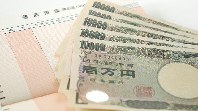 預金通帳と一万円札
