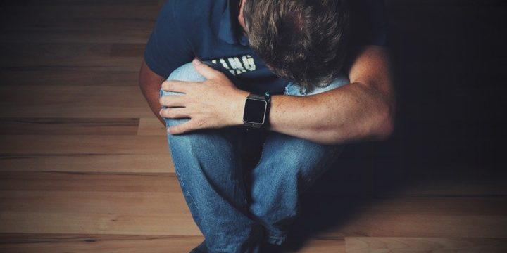 膝を抱える男性のイメージ