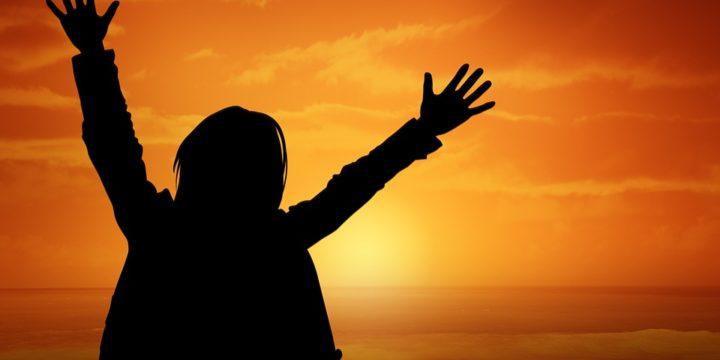 夕日を背景に手をあげる人のシルエット