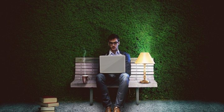 ベンチに座ってノートPCを使うビジネスマン