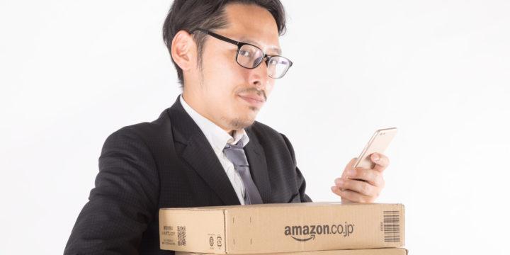 スマホと段ボール箱を持つビジネスマン