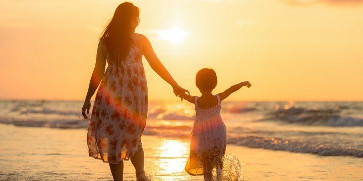 砂浜で手をつないで歩く親子