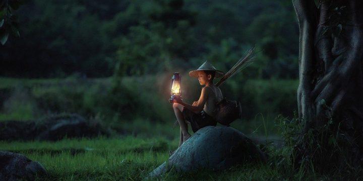 ランプの明かりを見つめる少年