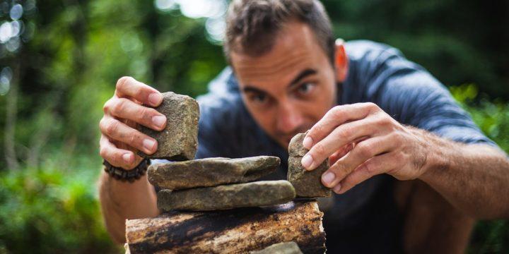 石を積み上げる男性