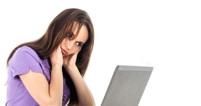 PCを見て首をかしげる女性