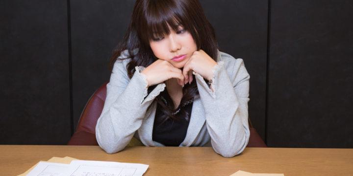 辞表と履歴書を見つめる女性