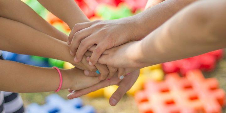 人々が手を重ね合わせるイメージ