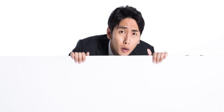 壁から覗き込む男性