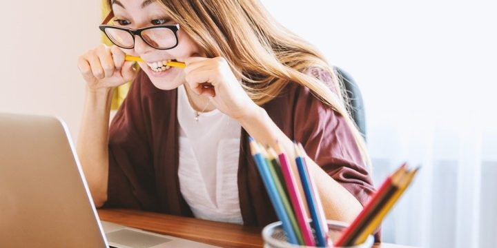 PCを見て鉛筆を噛みしめる女性