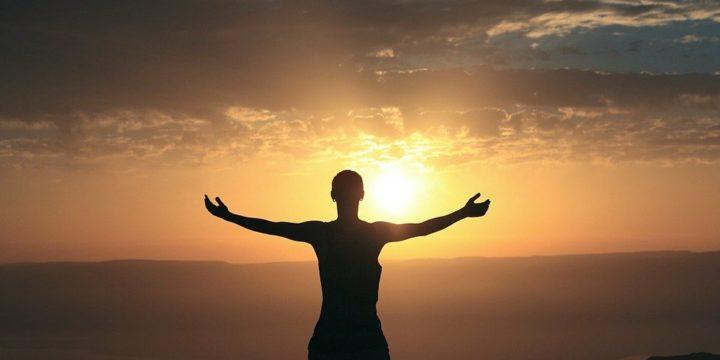 太陽に向かって手を広げる人物のシルエット