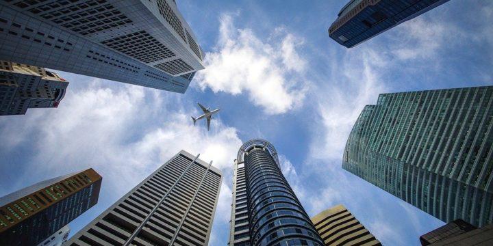 高層ビルの上空を飛ぶ飛行機