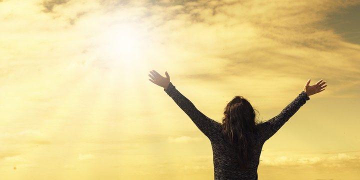 太陽に向かって両手を広げるシルエット