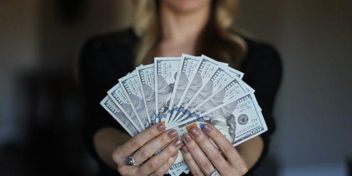 たくさんの紙幣を手に持つ女性