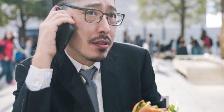 ハンバーガーを食べながら電話をする男性