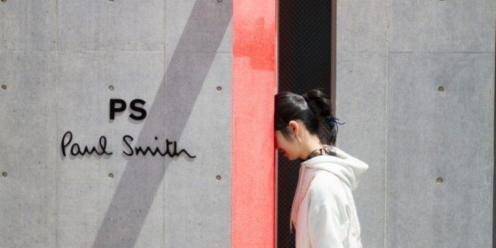 壁に頭をつける女性