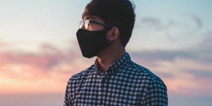 遠くを見つめるマスク姿の男性
